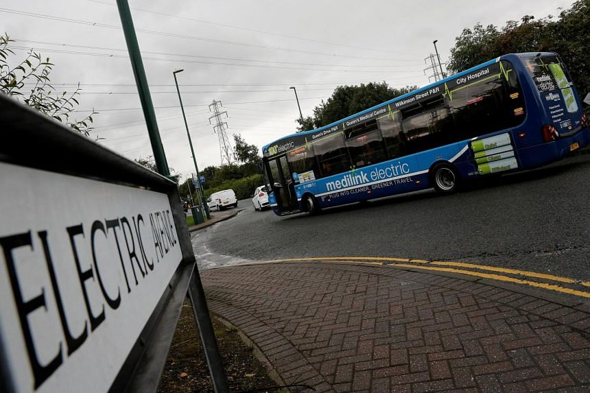 An electric bus is driven past Electric Avenue in Nottingham, Britain, on Aug 8, 2017.