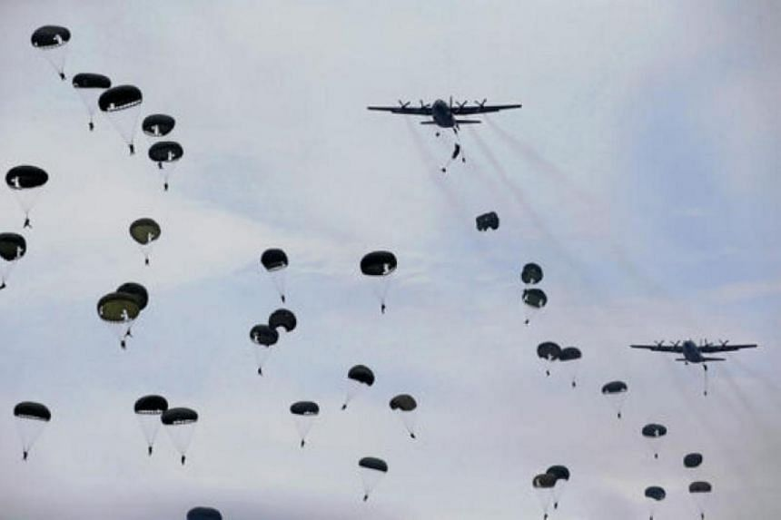 Indonesia soldiers jump from a Hercules C-130 military transport plane during an exercise at Ranai military airbase in Natuna Island, Indonesia, on Oct 6, 2016.
