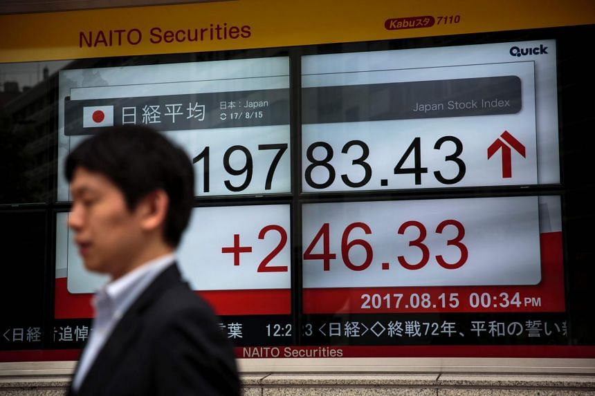 A man walks past a stock quotation board flashing in Tokyo on Aug 15, 2017.