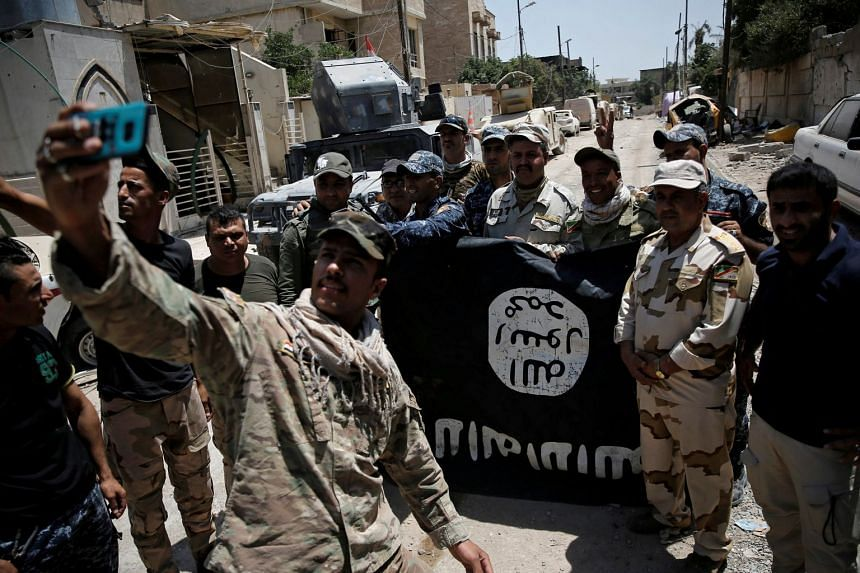 Iraqi soldiers take selfies with a captured ISIS flag after fighting militants in western Mosul, Iraq, June 17, 2017.