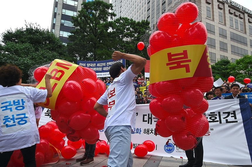 "South Korean activists bursting balloons with yellow banners reading ""ICBM"" and ""SLBM"" - the acronyms for intercontinental ballistic missile and submarine- launched ballistic missile - during a rally in Seoul yesterday to denounce North Korea's sixth"
