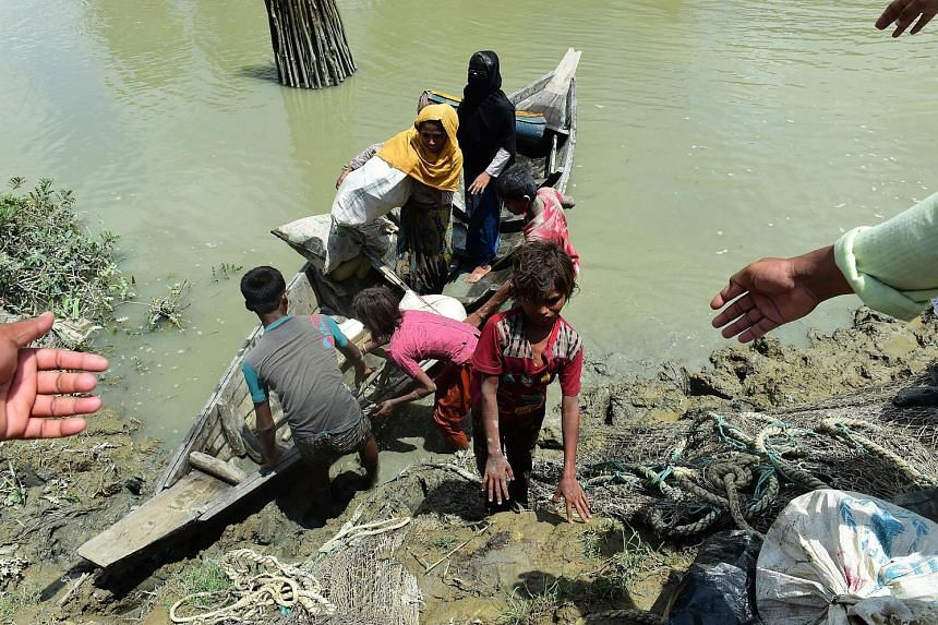 Bangladeshis helping Rohingya Muslim refugees to disembark from a boat on the Bangladeshi side of Naf River yesterday.