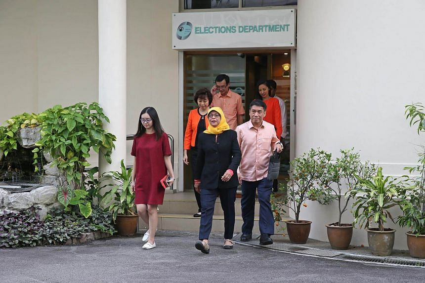 Madam Halimah Yacob (centre) steps out of the Elections Department after collecting her papers, on Sept 11, 2017.