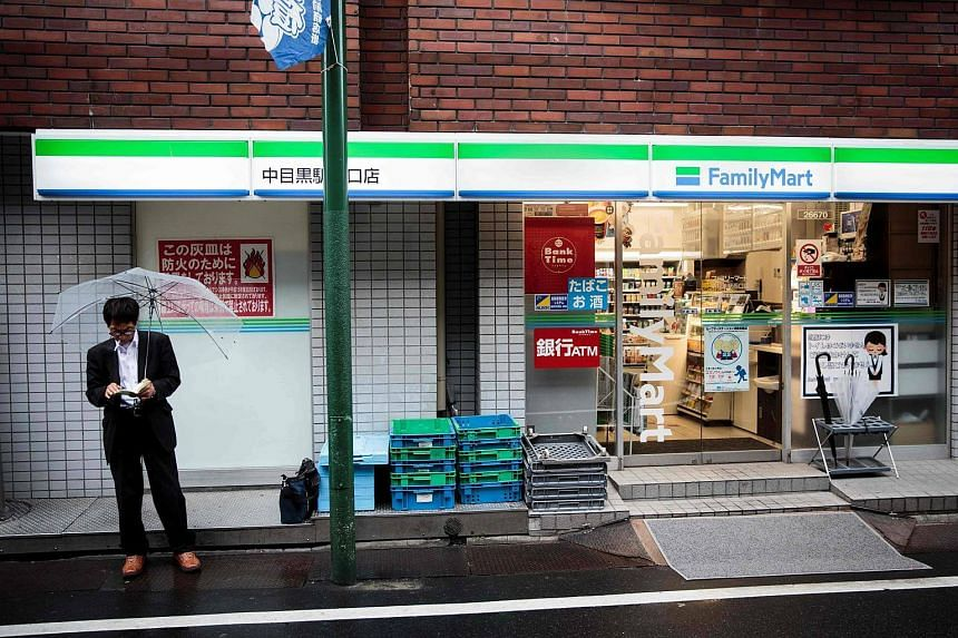 A man reads a book as he smokes next to a convenience store in the Nakameguro district in Tokyo.