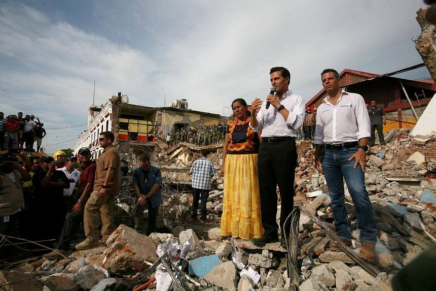Mexico's President Enrique Pena Nieto (second, right) addresses residents after an earthquake struck off the southern coast of Mexico late on Thursday, in Juchitan, Mexico, on Sept 8, 2017.