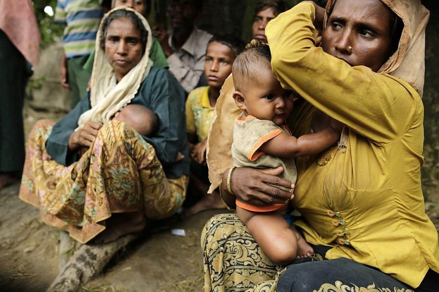 Rohingya refugees sit on a street as they look for shelter in Ukhiya, Cox's Bazar, Bangladesh, on Sept 11, 2017.