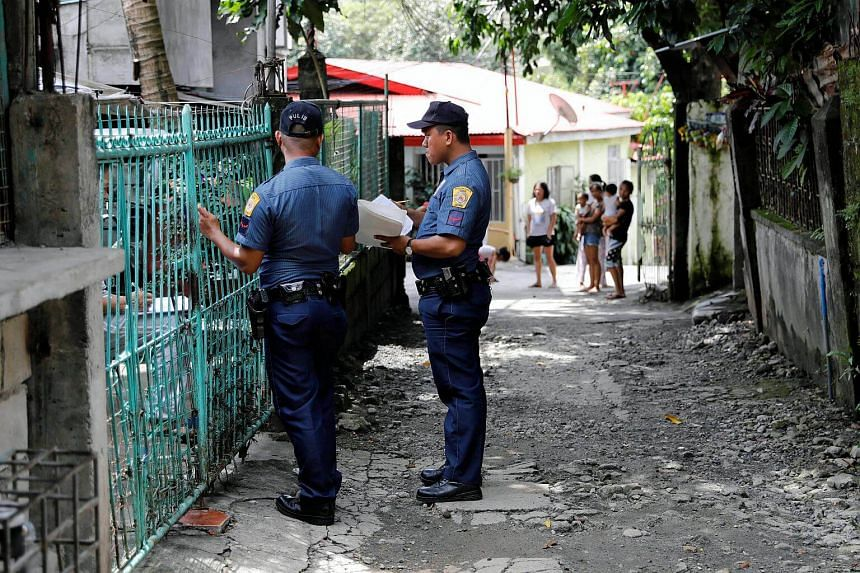 Policemen knock door to door and interview residents during a drug testing operation in Payatas, Quezon City, on Aug 23, 2017.