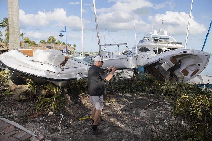 A woman photographs damage and boats brought onto land by Hurricane Irma at a marina in Miami, on Sept 11, 2017.