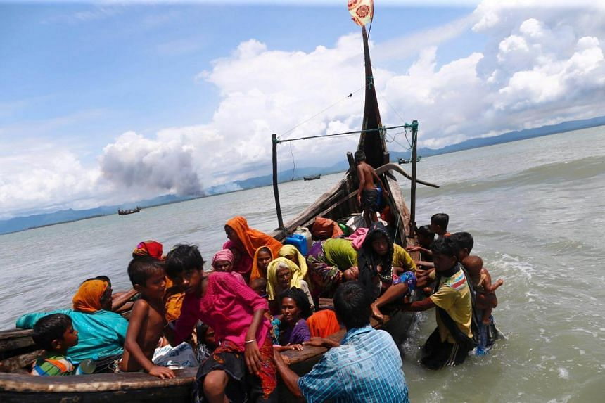 Smoke is seen on Myanmar's side of border as Rohingya refugees get off a boat after crossing the Bangladesh-Myanmar border through the Bay of Bengal in Shah Porir Dwip, Bangladesh, on Sept 11, 2017.