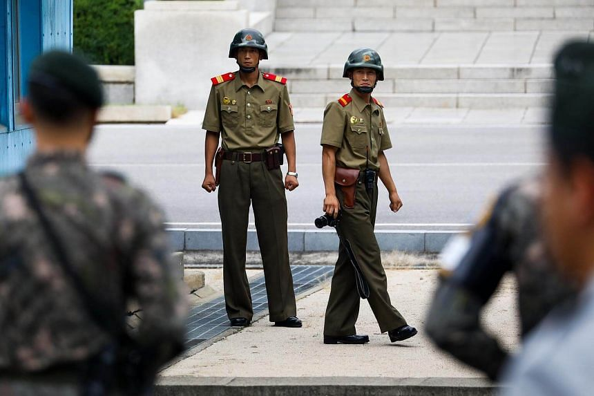 North Korean soldiers look towards the South Korean side of the truce village of Panmunjom in the Demilitarized Zone (DMZ) in Paju, South Korea, on July 27, 2017.