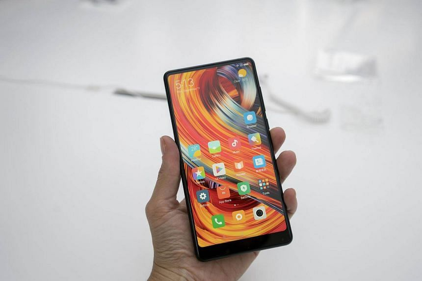 An attendee holds the Xiaomi Mi Mix 2 smartphone during a launch event in Beijing, China, on Sept 11, 2017.