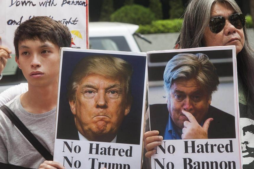 Anti-Steve Bannon protestors hold placards outside the venue of the 'Credit Lyonnais Securities Asia' (CLSA) Investors Forum 2017.