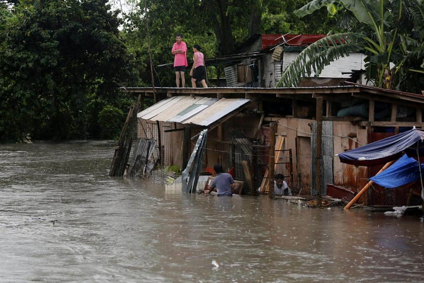 Filipino residents are seen at a flooded community in Bacoor city, Cavite province, Philippines on Sept 12, 2017.