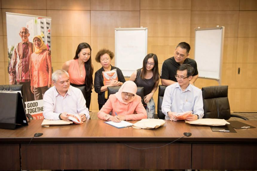 Madam Halimah Yacob penning a personal letter to Singaporeans as her campaign team looks on.