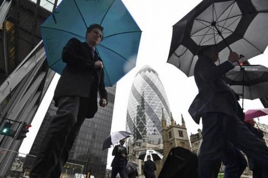 City workers walk in the rain in the financial district of the City of London.