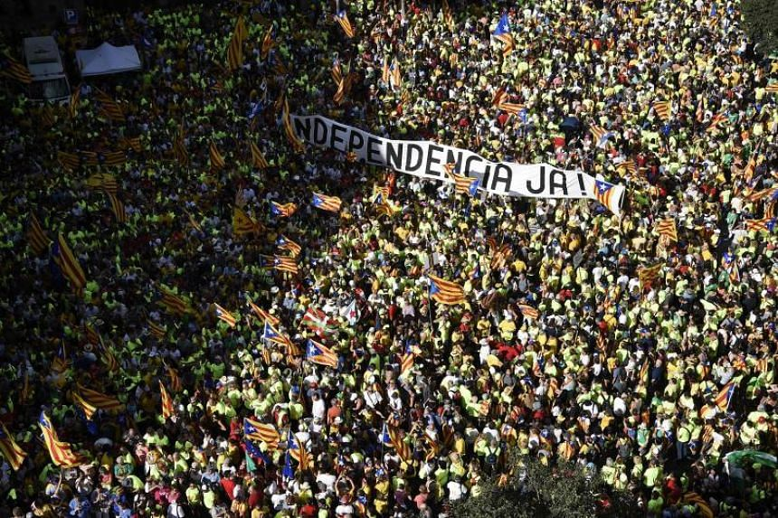 """People hold a banner reading """"Independence now!"""" in Catalan at a pro-independence demonstration in Barcelona on Sept 11, 2017."""