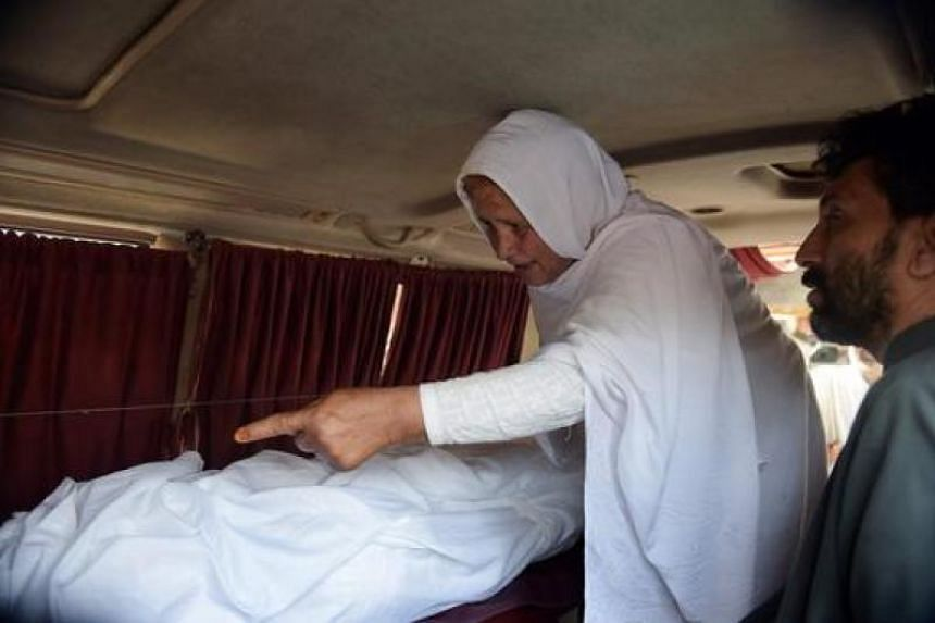 Pakistani grandmother of a young woman who was tortured and set alight, mourns next to her body in an ambulance outside a hospital in Islamabad on June 1, 2016.