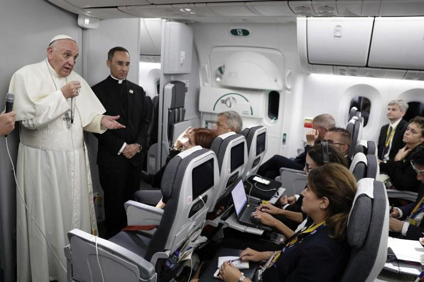 Pope Francis (left) talks to journalists during a press conference on board his flight to Rome at the end of a five-day visit to Colombia on Sept 11, 2017.