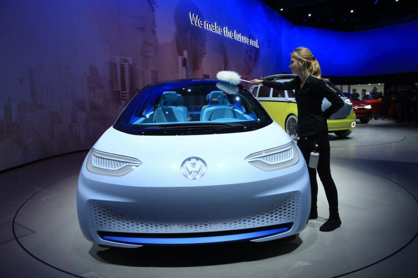 An employee dusts the top of a Volkswagen AG (VW) I.D. electric automobile on display ahead of the IAA Frankfurt Motor Show on Sept. 11, 2017.