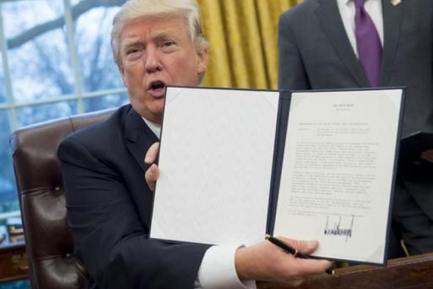 US President Donald Trump holds up an executive order withdrawing the US from the Trans-Pacific Partnership after signing it on Jan 23, 2017.