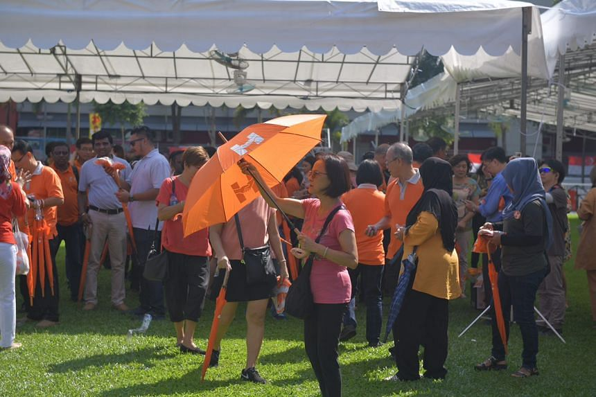 Supporters with orange umbrellas arrive at the People's Association HQ in King George's Avenue on Sept 13, 2017.