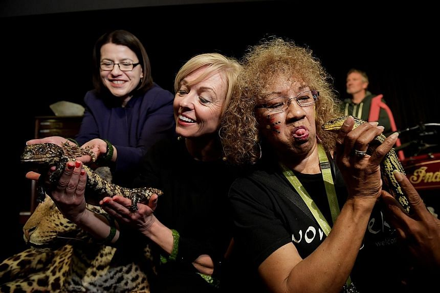 "From left: Australia's Minister for Families and Children Jenny Mikakos, Museums Victoria CEO Lynley Marshall and tour guide Victoria Barnett getting up close with lizards at the launch of the ""Museum Inside Out"" exhibition at Melbourne Museum, Victo"