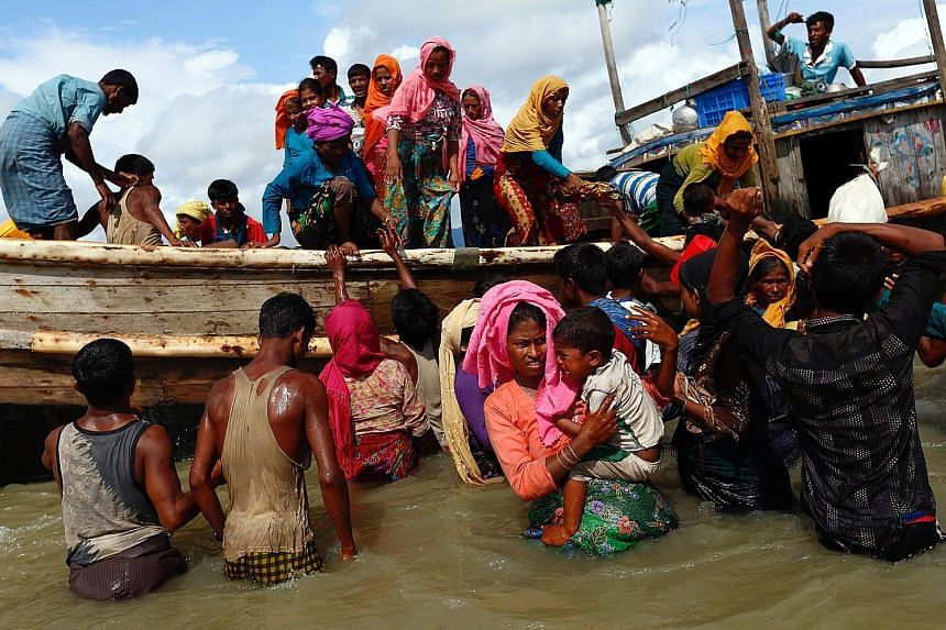 Rohingya refugees getting off a boat in Shah Porir Dwip, Bangladesh, on Monday. More than 300,000 Rohingya have poured into Bangladesh since Aug 25, adding to around 300,000 refugees already living in overflowing camps run by the United Nations in Co