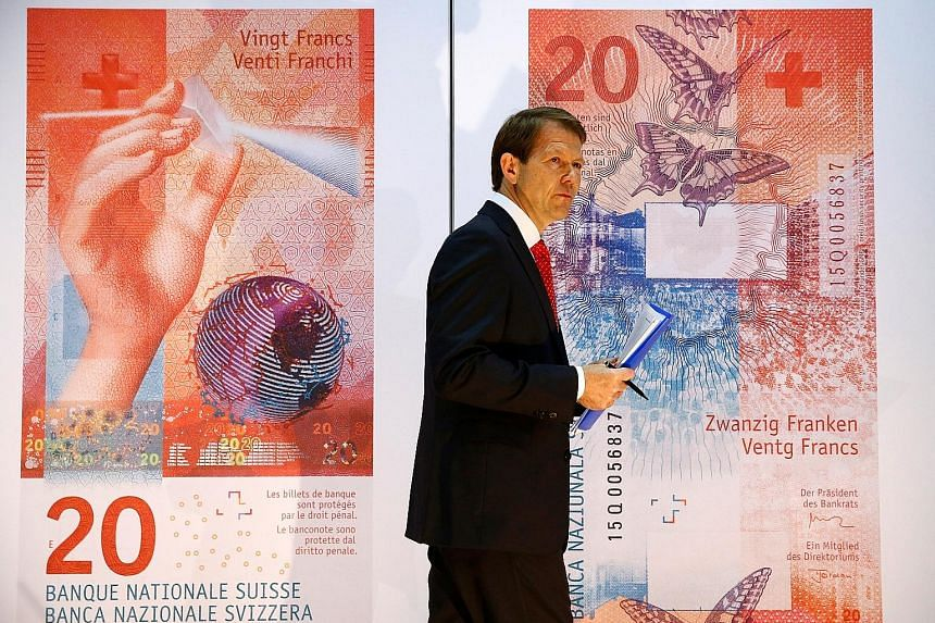 """Swiss National Bank vice-chairman Fritz Zurbruegg against a backdrop of new Swiss Franc notes. The weakening of the currency may reduce its """"significant overvaluation""""."""
