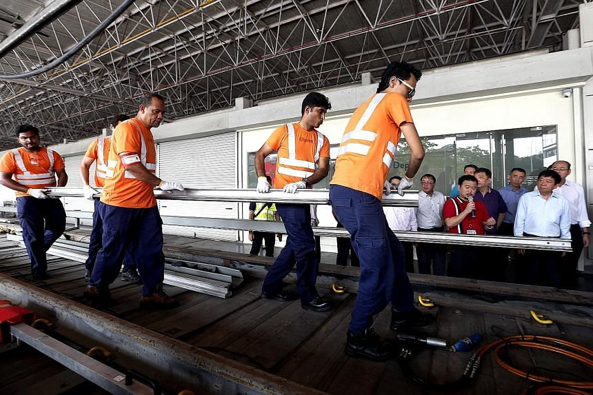Transport Minister Khaw Boon Wan (at right) watching a demonstration of the power rail replacement at Bishan Depot yesterday. A ceremony was held to mark the completion of the second major renewal project for the North-South and East-West lines - the