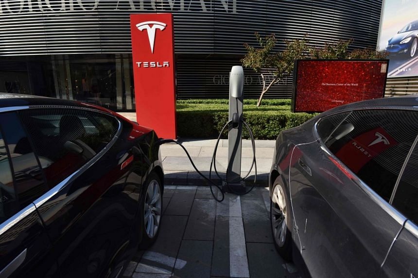 Tesla cars charge at a Tesla charging station outside a shopping mall in Beijing, Sept 12, 2017.