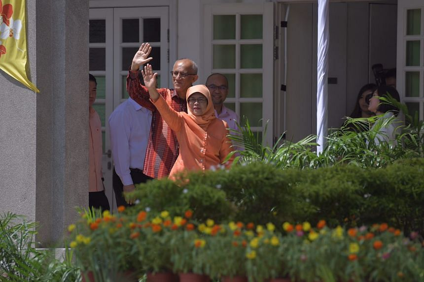 Madam Halimah Yacob and her husband Mohamed Abdullah Alhabshee waving at supporters as they make their way into the nomination centre on Sept 13, 2017.