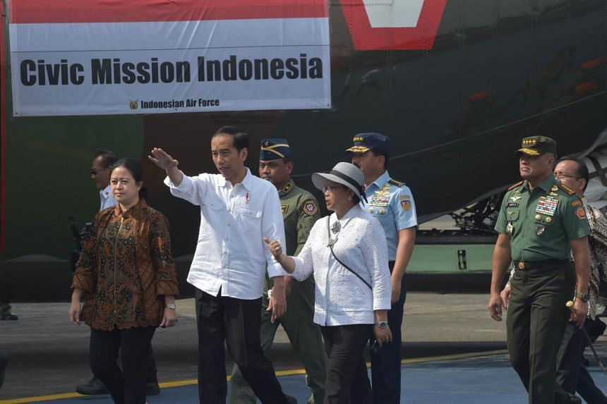 Indonesia's President Joko Widodo (centre) walks on the tarmac as Indonesian soldiers load sacks of government food aid onto an air force C-130 aircraft, bound for Bangladesh and its cargo destined for Rohingya refugees fleeing violence in Myanmar, a