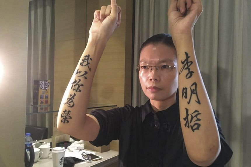 Lee Ching-yu, wife of Taiwanese human rights activist Lee Ming-che, displaying tattooed words on her arms reading from Chinese 'I Am Proud of You' (left) 'Lee Ming-che' (right) after attending her husband's trial.