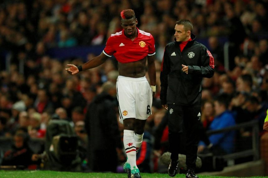 Manchester United's Paul Pogba walks off as he is substituted for Marouane Fellaini after sustaining an injury.