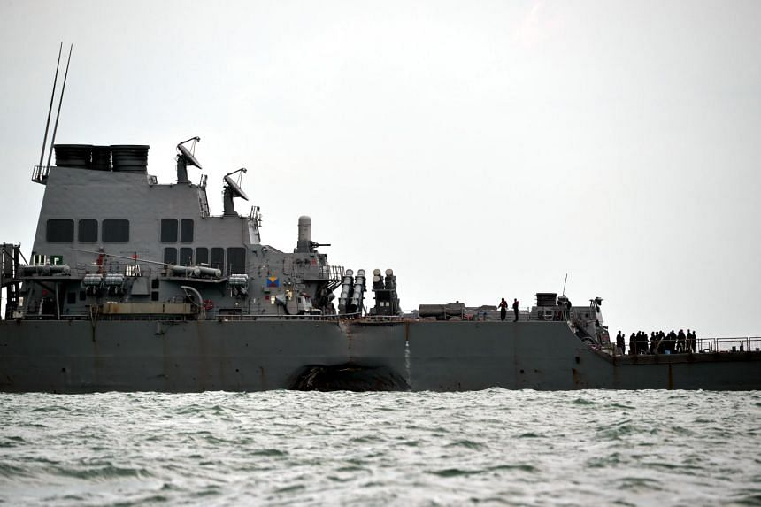 The guided-missile destroyer USS John S. McCain with a hole on its left portside after a collision with an oil tanker, outside Changi naval base in Singapore on Aug 21, 2017.