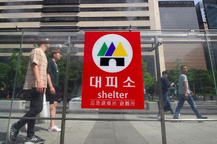 Pedestrians walk past a shelter sign set up on an exit of a subway station in Seoul on Sept 4, 2017.
