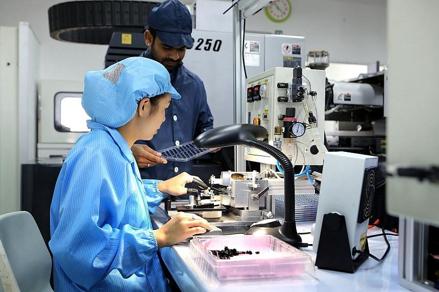 Home-grown optics manufacturer Moveon Technologies relies heavily on advanced manufacturing machines to produce ever-smaller lenses and devices. Infineon employees inputting jobs on an automated guided vehicle. The introduction of new workflow, techn