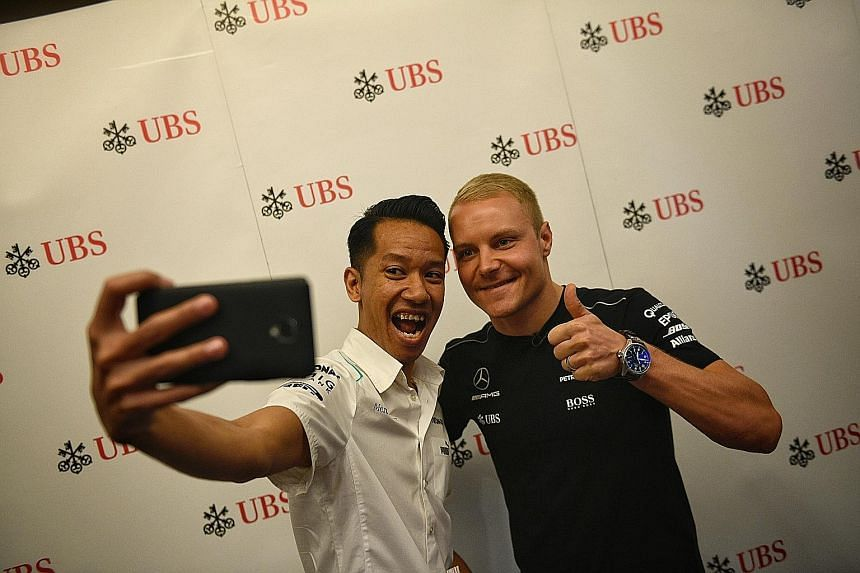 ST reader Ruslan Rusli Lim posing for a wefie with Mercedes driver Valtteri Bottas at a UBS event. While the Finn trails team-mate Lewis Hamilton and Ferrari's Sebastian Vettel by a large margin, he will not give up.