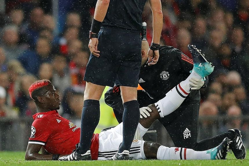 Manchester United's Paul Pogba receiving medical attention for an injury suffered during the 3-0 Champions League victory against Basel at Old Trafford on Tuesday. It was the Frenchman's first game as United captain.