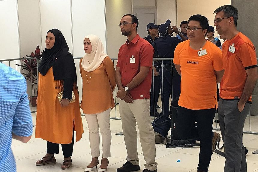 Above: With Madam Halimah at the nomination centre yesterday were (from left) daughter Sharifah Bahiyah, daughter-in-law Amal Nasibah, son Syed Isa, son-in-law Mohd Karno and son Syed Ali. Left: The crowd showing their support for the President-elect
