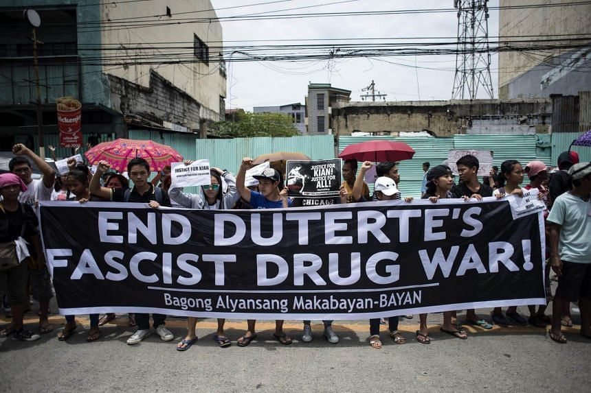 Protesters hold anti extra-judicial killing banners during the funeral march for 17-year-old student Kian Delos Santos, who was killed allegedly by police officers during an anti-drug raid, in Manila on Aug 26, 2017.