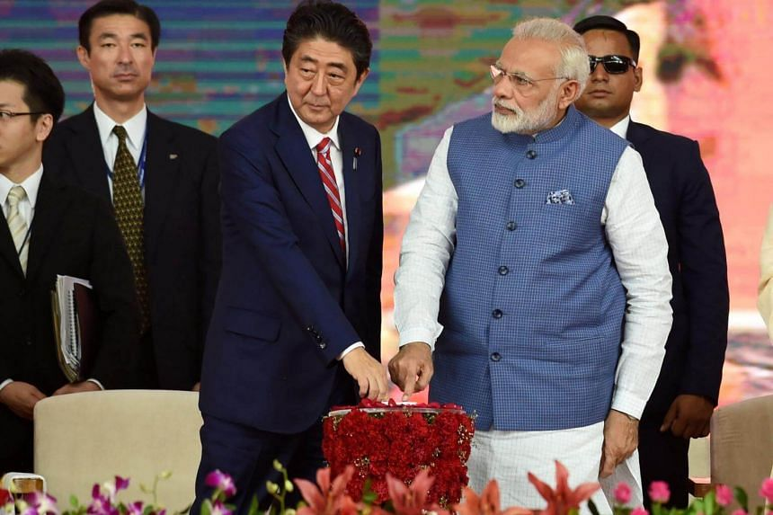 Japanese Prime Minister Shinzo Abe and his Indian counterpart Narendra Modi pushing switches during the groundbreaking ceremony for the new high-speed rail project in Ahmedabad on Sept 14, 2017.