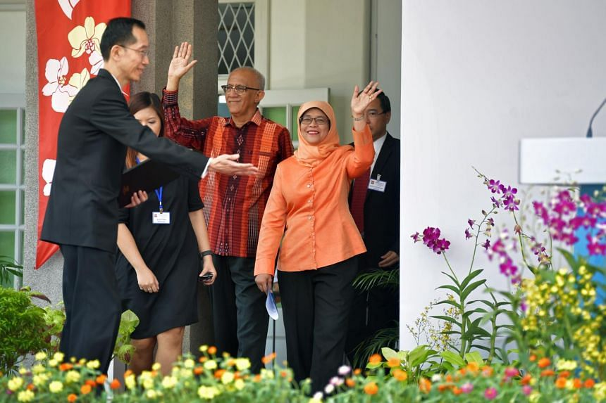 Returning Officer Mr Ng Wai Choong, the chief executive of the Energy Market Authority, directing Madam Halimah Yacob together with her husband, Mr Mohammed Abdullah Alhabshee on stage at the People's Association HQ in King George's Avenue.