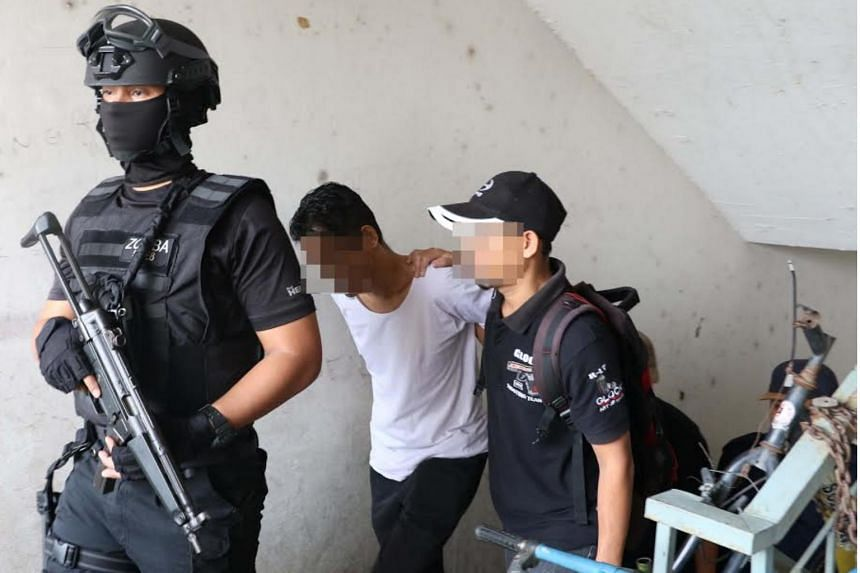 Malaysia's anti-terrorism unit escorting a 41-year-old bus driver in Petaling Jaya, Selangor on Sept 10, 2017. The man had planned to join ISIS in Syria later this year.