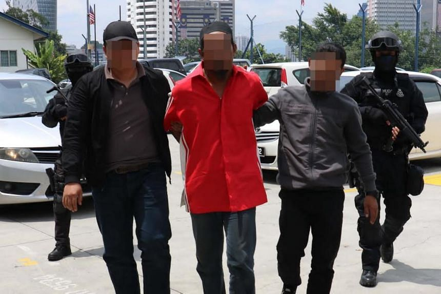 A 38-year-old Cendol seller being escorted by Special Branch Counter-Terrorism Division officers after a raid in Melaka on Sept 10, 2017. The man had planned joining the ISIS faction in southern Philippines and in Rakhine, Myanmar.