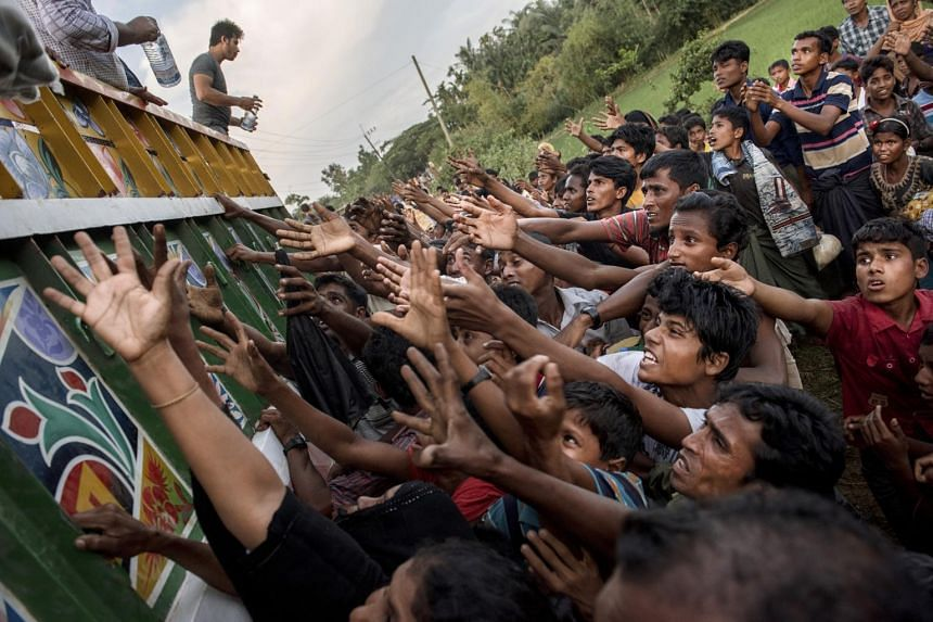 Rohingya people reach out to collect food and water rations at a newly set-up refugee camp at Balukhali in Cox's Bazar, Bangladesh on Sept 12, 2017.