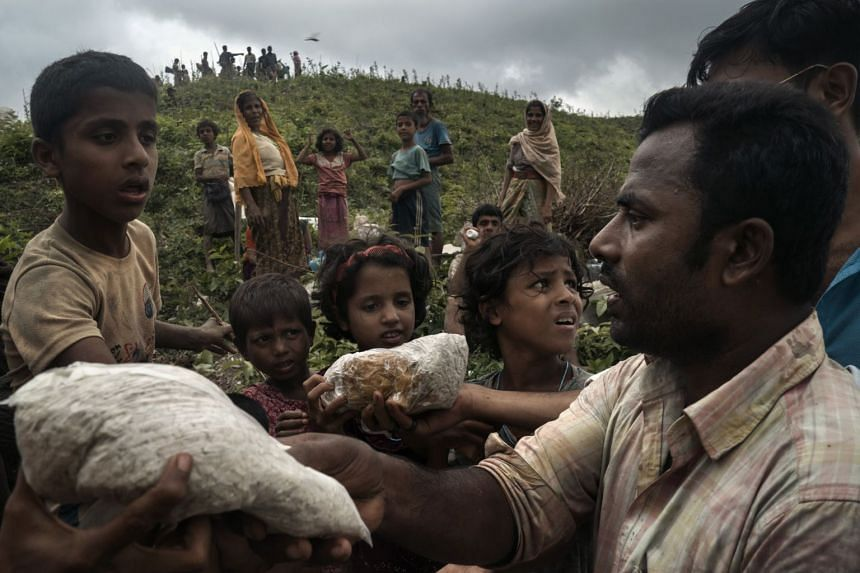 Residents hand out food aid to Rohingya refugees after they crossed the border from Myanmar, near Gundum, Bangladesh, Sept 3, 2017.