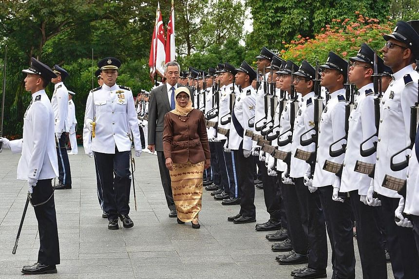 President Halimah Yacob, accompanied by Prime Minister Lee Hsien Loong, inspecting the guard of honour during the welcome ceremony for the new President at the Istana yesterday.