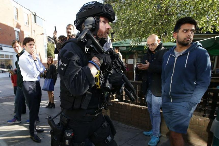 Armed British police officers stand on duty outside Parsons Green underground tube station in west London on Sept 15, 2017, following an incident on an underground tube carriage at the station.