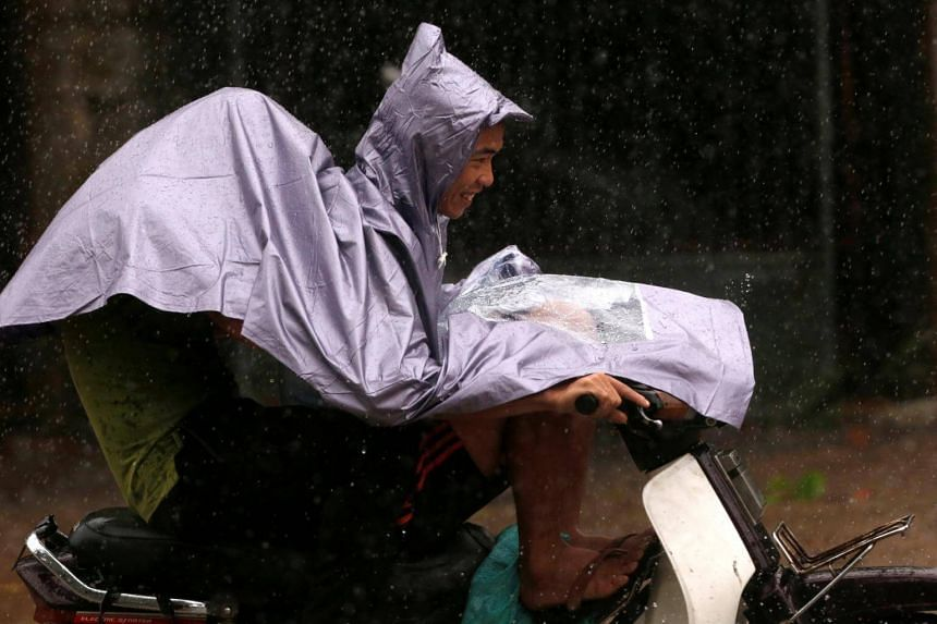 People ride a motorbike while the Doksuri storm hits in Ha Tinh province, Vietnam on Sept 15, 2017.